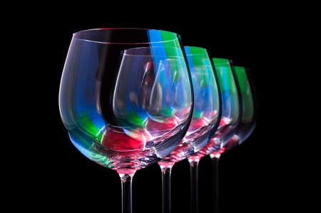 Nightclub wine glasses lit by red, green, blue party lights, nightlife and entertainment industry, four objects in row isolated on black background