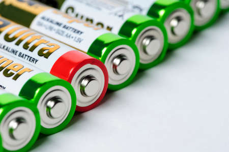 Moscow, Russia - January 04, 2016: Used alkaline batteries AA size format with green top and one with red top lying in a row, selective focus, studio shot Editorial