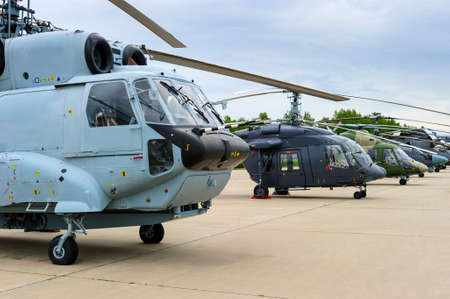 Military helicopters in row standing on runway, air force ready to attack, modern army aviation and aerospace industry