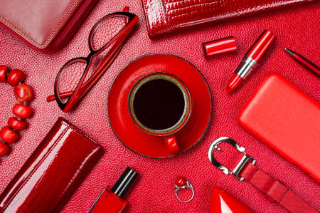 Woman red accessories with coffee, cosmetic, jewelry, gadget and other objects on leather background, fashion industry, modern female concept, selective focus