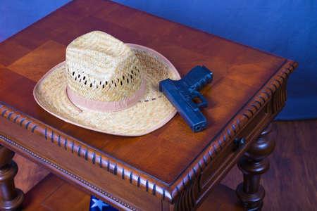 帽子と木製の机の上の拳銃 写真素材