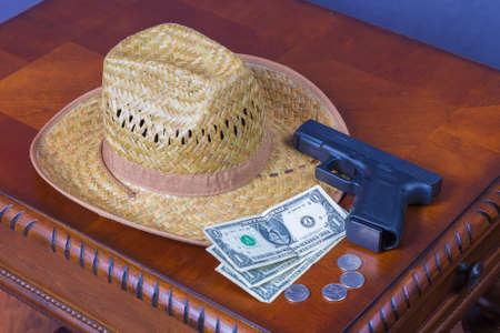 Hat, handgun and money on wooden desk Stock Photo