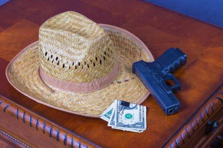 帽子、拳銃や木製の机の上のお金