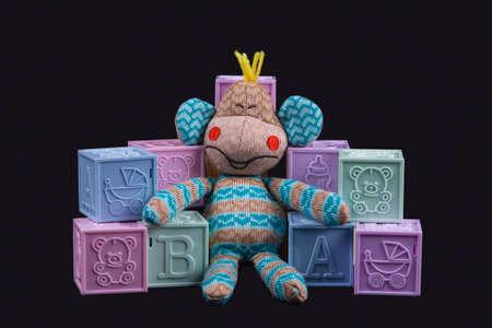 Socks toy monkey sits on bricks on black background photo
