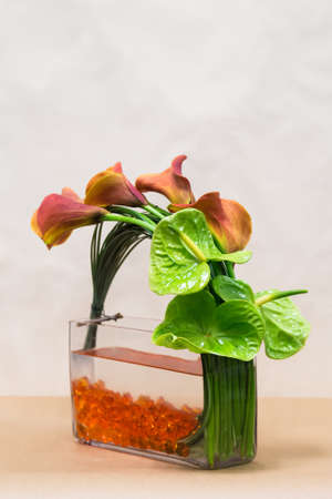 Floral arangement with twisted Mango Calla Lilies, green Anthurium  and greenery on a bed of orange gems photo