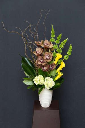 Arangement floral con lirios de cala, Cymbidium y James Storey orquídeas, hortensias, sauce rizado, Moluccella y zonas verdes en florero cilindro blanco Foto de archivo - 31256869