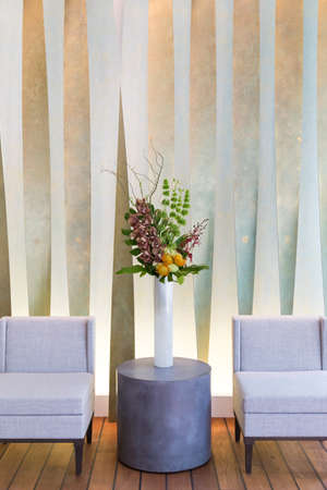 Floral arangement with Cymbidium and James Storey orchids, Hydrangea, Curly willow, Yellow pin cushion protea and greenery in white cylinder vase, and two beige chairs photo