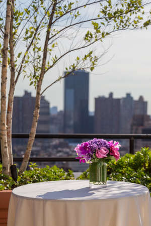 Floral arangement with pink Roses, Hydrangea, James Storey and Vanda Orchids on city background from rooftop photo