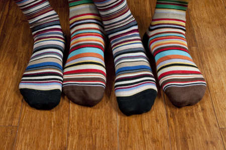 stockings feet: His and hers striped socks on wooden floor