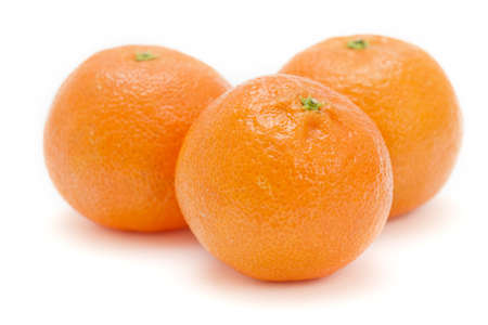 Three satsumas on a white background