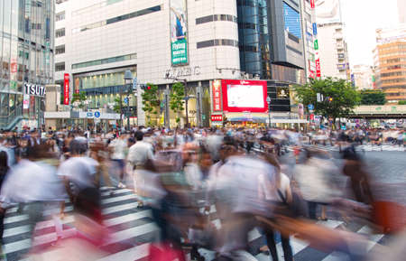 TOKYO, JAPAN - MAY 13, 2015: Pedestrians walk at Shibuya Crossing during the holiday season. The scramble crosswalk is one of the largest in the world. Editorial
