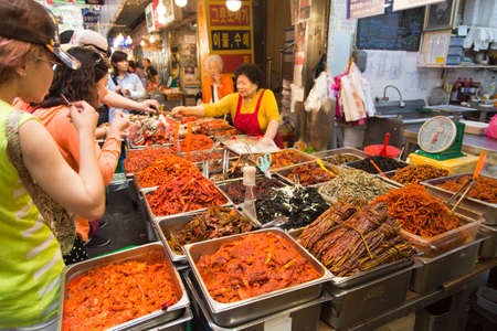 Seoul, Republic of Korea - 5 May 2015: People queing and tasting the food on a stall in Gwangjang Market in Seoul, Korea
