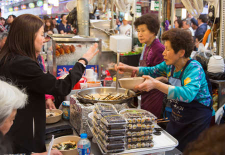 korean culture: Seoul, Republic of Korea - 5 May 2015: People queing and tasting the food on a stall in Gwangjang Market in Seoul, Korea