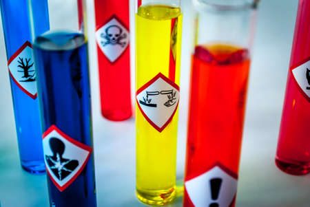 oxidising: Multicolored Chemistry vials - Focus on corrosive danger Stock Photo
