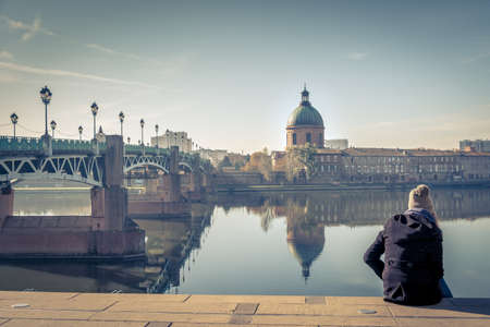 Saint-Pierre Bridge reflecting in Garonne river and Dome de la Grave with a young student in Toulouse, France Imagens