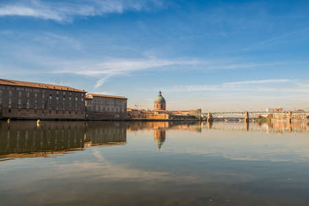 Hospital de La Grave on a sunny day reflected in Garone river. Toulouse, France