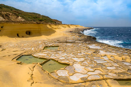 Salt evaporation ponds, also called salterns or salt pans located near Qbajjar on the maltese Island of Gozo. 免版税图像