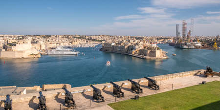 Panorama, skyline of the Maltese capital city Valletta. The Saluting Battery of La Valletta and Fort St. Angelo of La Vittoriosa in Malta Imagens