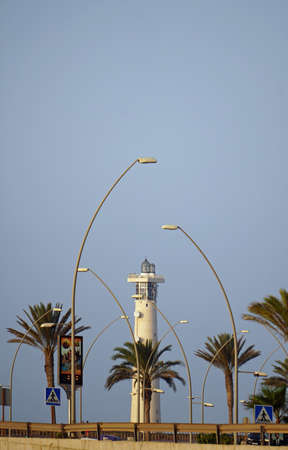 Lighthouse. View through the expressway with lighting masts. The palms. Reklamní fotografie
