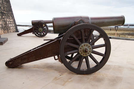 Ancient copper cannon in front of a stone fortress
