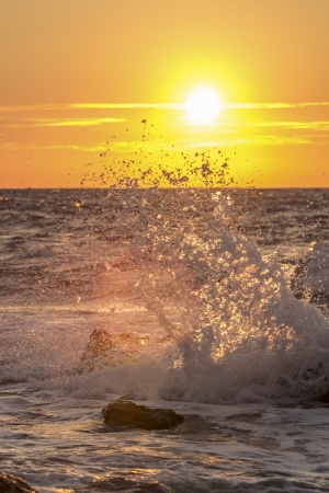 Bright sunset under the sea with waves splashes photo