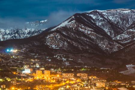 Night snow mountain city light landscape with clouds photo