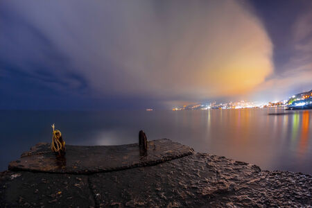 Night landscape to the city lights in clouds near the sea clolrful photo