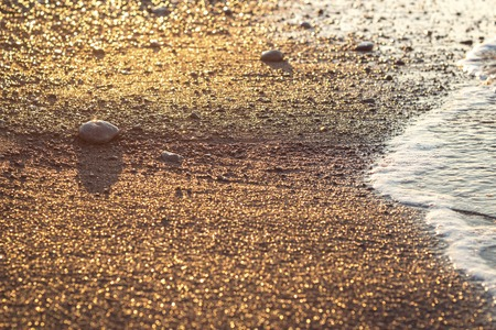 Sea wave on sand and stone at sunrise colorful photo