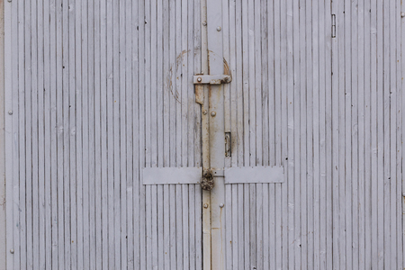 staining: Old rusty metal padlock hanging on a weathered wooden door with rust staining the planks fill all frame