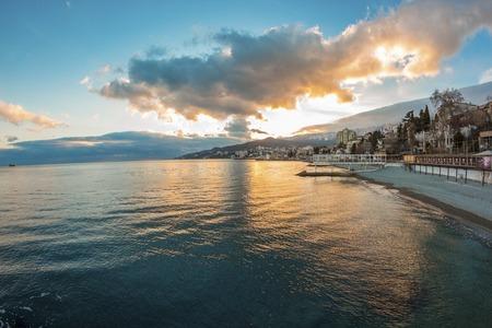 Beautiful sunset over the sea with mountain city, Yalta, Crimea, Russia photo