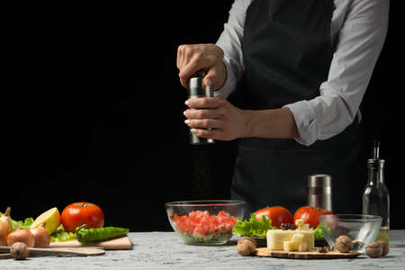 The chef prepares a salad, with a Pepper mill on a dark background with an empty space for writing Stock Photo
