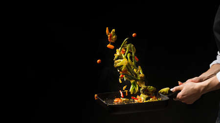 The chef prepares. Black background for copy text.Concept cooking Banco de Imagens