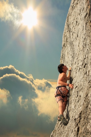 A guy climbs on a rock against the sky with a sunset