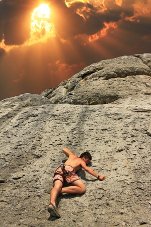 A guy climbs on a rock against the sky with a sunset photo