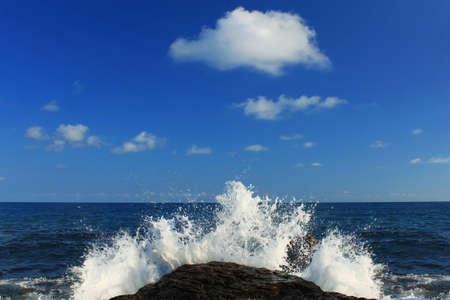 Ocean waves crash against a rock photo