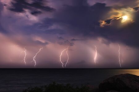 Severe thunderstorm over the ocean. Moonlight Stock Photo