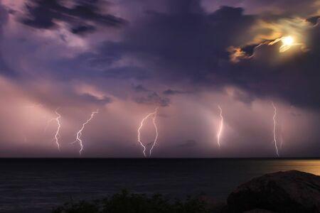 Severe thunderstorm over the ocean. Moonlight Stock Photo