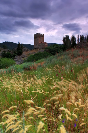 The tower of a medieval castle on the background of stormy skies photo