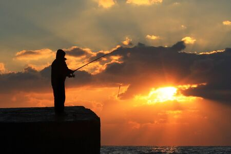 Fisherman standing on a pier at dawn sky background with sun rays photo