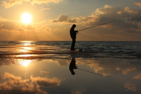 outdoorsman: Fisherman standing on a pier at dawn sky background with sun rays and reflected in the sea water