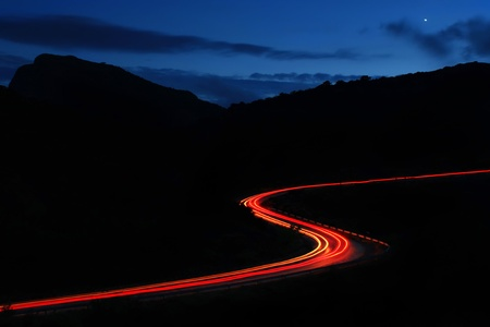 Night roads in the mountains with a stream of cars
