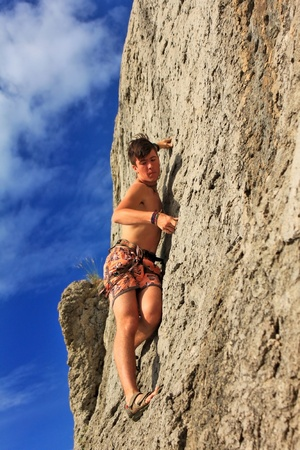 Rock climber on a rock against the blue sky photo