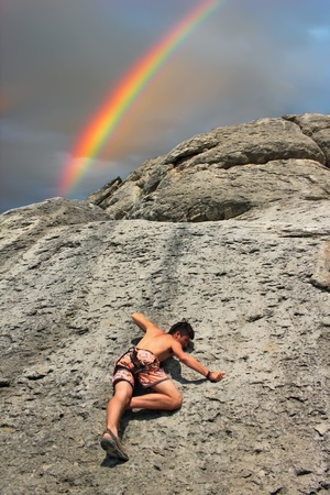 A rock climber on a cliff on the background of the rainbow  photo