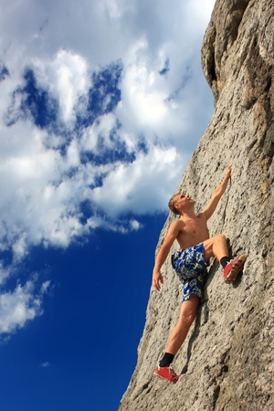 Rock climber on a rock against the blue sky photo