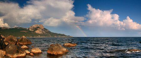Rainbow over stormy sea photo