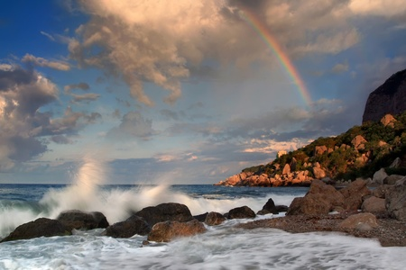 Rainbow over stormy sea in the early morning