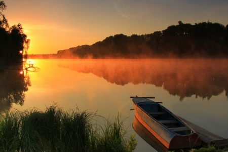 Boat on the shore of a misty lake on a summer morning  Standard-Bild