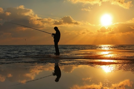 Fisherman standing on a pier at dawn sky background with sun rays and reflected in the sea water photo