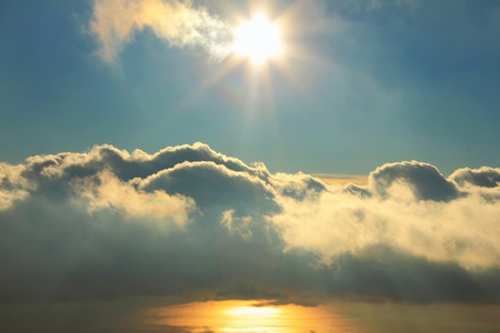 Cloudy sky with the sun over the sea