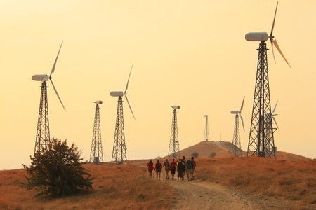 Group of people walking through fields with wind generators photo